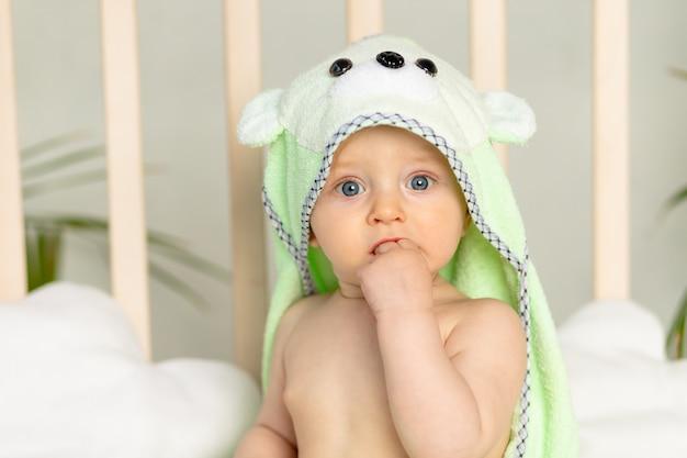 Retrato de um menino em uma toalha verde após um banho na cama em casa com um dedo na boca