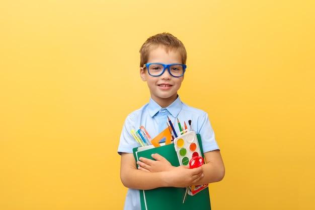 Retrato de um menino engraçado, alegre e sorridente, de camisa azul com livros e artigos de papelaria nas mãos.