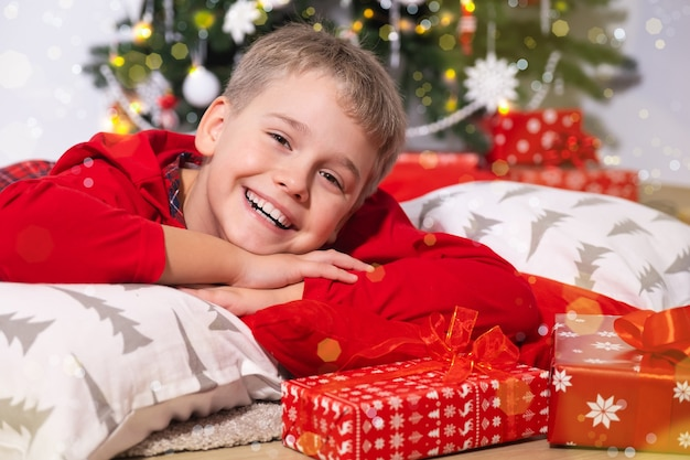 Retrato de um menino engraçado e sorridente, olhando para a câmera, cercado de presentes
