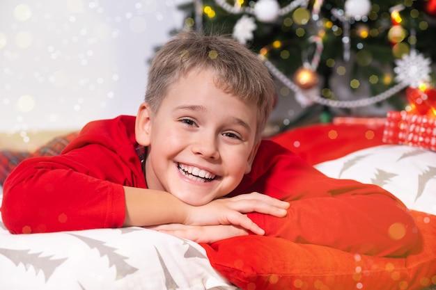 Retrato de um menino engraçado e sorridente, olhando para a câmera, fica perto da árvore de natal