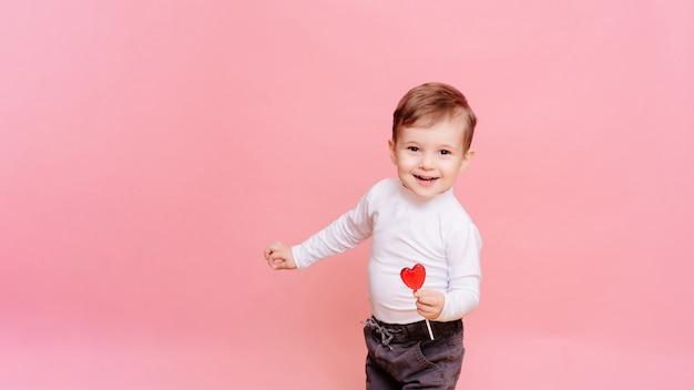 Retrato de um menino feliz com um pirulito em forma de coração na mão.