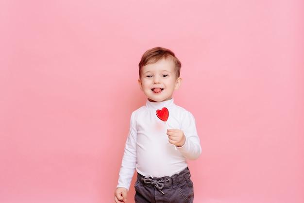 Retrato de um menino feliz com um pirulito em forma de coração.