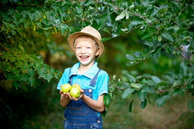Retrato de um menino feliz de seis anos com roupas azuis e chapéu em um jardim com macieiras