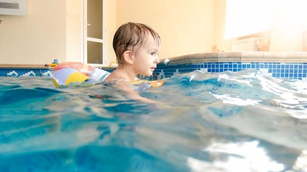 Retrato de um menino feliz e alegre brincando com uma bola de praia inflável e um anel colorido na piscina interna da casa