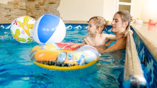 Retrato de um menino feliz rindo com uma jovem mãe brincando com uma bola de praia inflável colorida na piscina de um hotel resort de verão