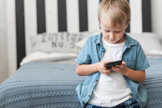 Retrato, de, um, menino, ficar, frente, cama, usando, telefone pilha