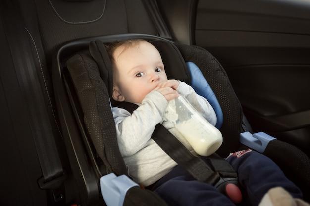 Retrato de um menino fofo bebendo leite na cadeirinha do carro