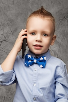 Retrato de um menino fofo com camisa azul e gravata borboleta com telefone celular contra textura cinza em estúdio