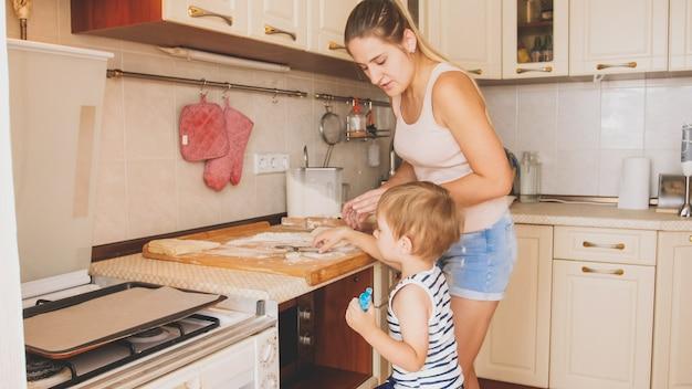 Retrato de um menino fofo de 3 anos cozinhando biscoitos com a mãe