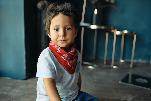 Retrato de um menino fofo gordinho mestiço com cabelo encaracolado e pele escura sentado no chão em casa usando um pano vermelho no pescoço, com uma expressão facial triste