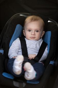 Retrato de um menino fofo sentado na cadeira de segurança do carro