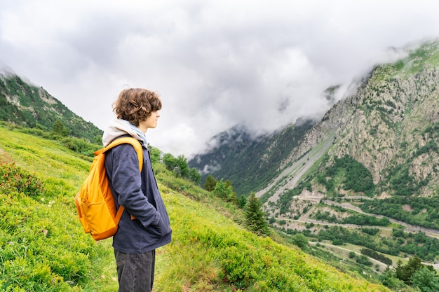 Retrato de um menino jovem adolescente com cabelos cacheados, com mochila amarela em uma jaqueta preta de pé nas montanhas nos alpes franceses, olhando para longe com prazer. atividades de caminhadas no verão.