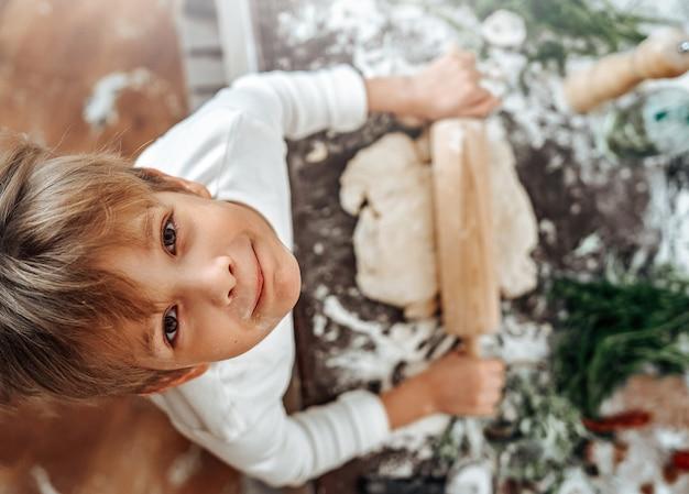 Retrato de um menino jovem e sorridente em camisas brancas, ele olha para a câmera e rola uma massa preparando comida na cozinha.
