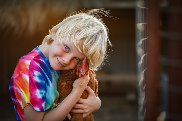 Retrato de um menino loiro branco com uma camisa colorida abraçando uma linda galinha