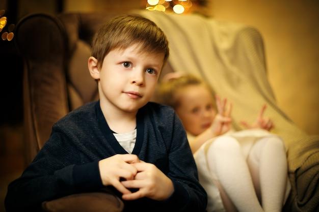 Retrato de um menino loiro de 5 a 7 anos em uma cadeira com uma irmãzinha fora de foco