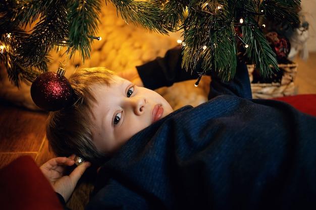 Retrato de um menino loiro de 57 anos deitado no chão perto da árvore do ano novo, olhando para a câmera