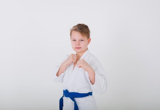 Retrato de um menino loiro em um quimono branco com uma faixa azul e as mãos protegidas em uma parede branca