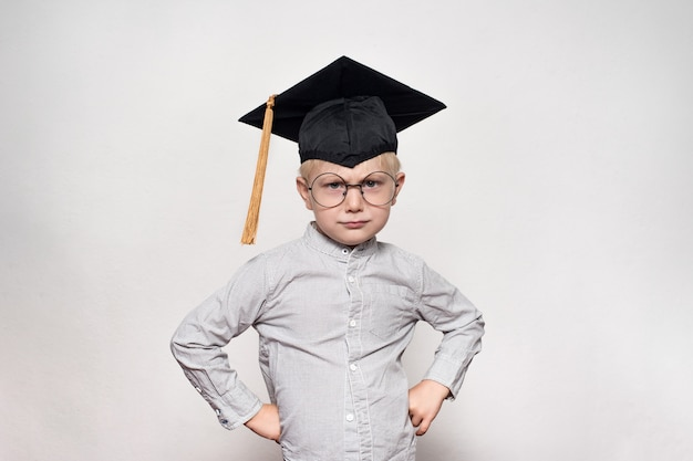 Retrato de um menino loiro sério de óculos grandes e um chapéu acadêmico. fundo branco.