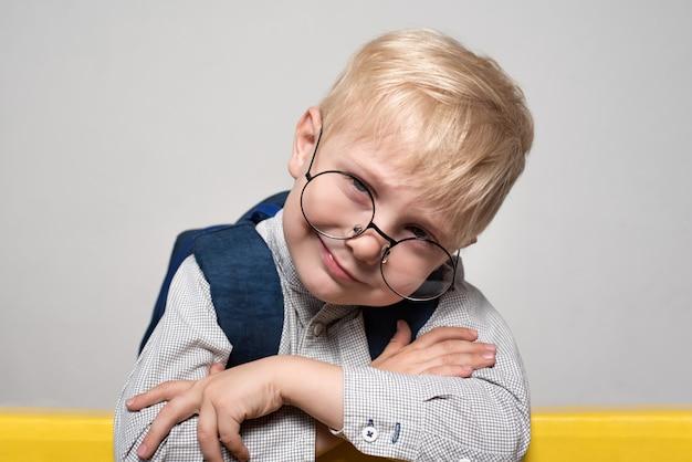 Retrato de um menino loiro sorridente em copos e com uma mochila escolar. conceito de escola