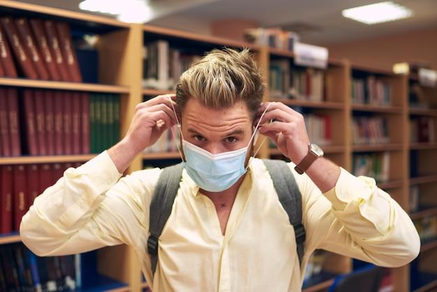 Retrato de um menino loiro usando uma máscara para entrar na biblioteca