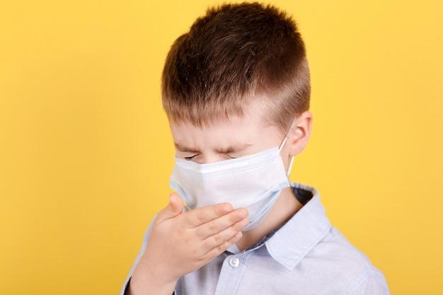 Retrato de um menino morena em máscara médica espirra.