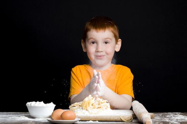 Retrato de um menino na cozinha enquanto ajuda a preparar a comida