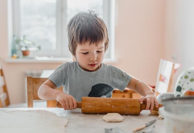 Retrato de um menino na cozinha usando o rolo de massa para preparar a massa para biscoitos