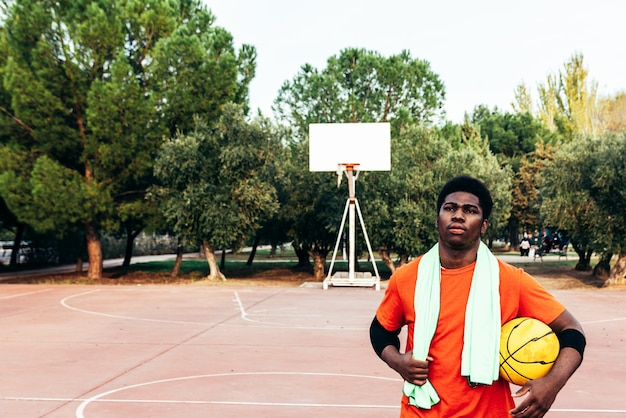 Retrato de um menino negro afro-americano com uma toalha verde nos ombros e uma bola amarela na mão andando em uma quadra de basquete urbana.