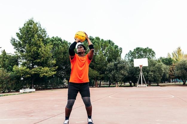 Retrato de um menino negro afro-americano jogando basquete em uma quadra urbana.