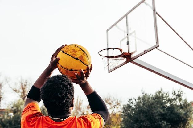 Retrato de um menino negro afro-americano pronto para atirar a bola na cesta.