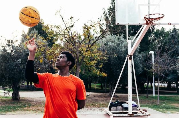 Retrato de um menino negro afro girando uma bola de basquete na mão. cesta de basquete em segundo plano.