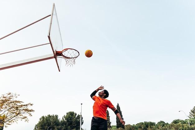 Retrato de um menino negro afro pulando na cesta para atirar a bola. jogando basquete em uma quadra urbana