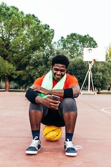 Retrato de um menino negro afro sentado em sua bola e usando seu telefone na quadra de basquete. tecnologia de conceito e esportes.