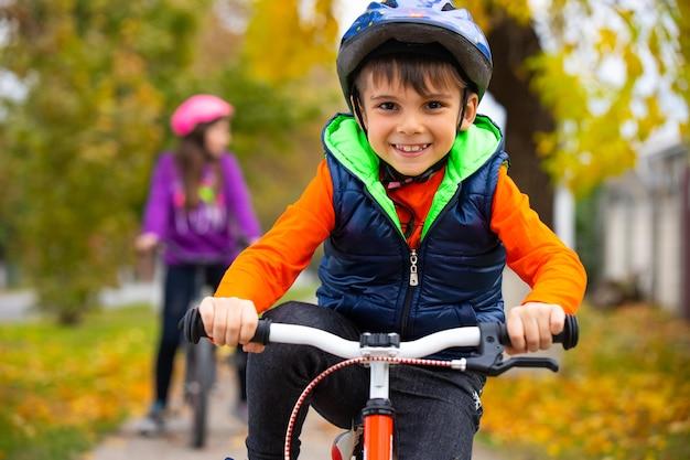 Retrato de um menino no parque com sua irmã na parede. criança pequena usando um capacete e andando de bicicleta em um dia de outono. esportes ativos e saudáveis ao ar livre.