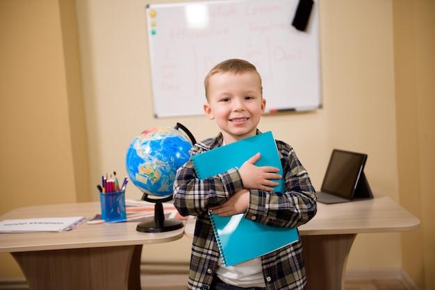Retrato de um menino olhando para a câmera na sala de aula.