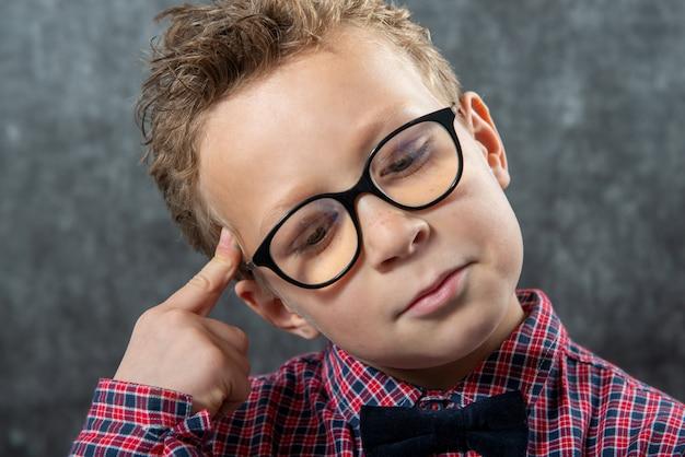 Retrato de um menino pensativo com óculos