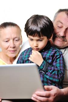 Retrato de um menino pequeno bonito usando laptop com seus avós