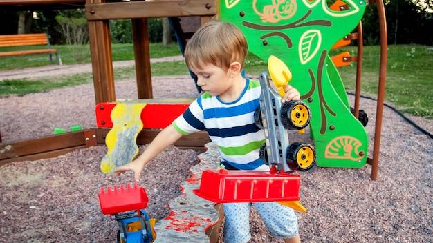 Retrato de um menino pequeno de 3 anos pegando seus brinquedos da caixa de areia no palyground