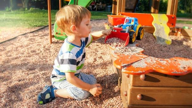 Retrato de um menino pequeno de 3 anos sentado no parquinho e cavando a areia com uma pá de plástico de brinquedo