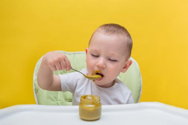 Retrato de um menino pequeno que está desfrutando purê de brócolis em um amarelo isolado