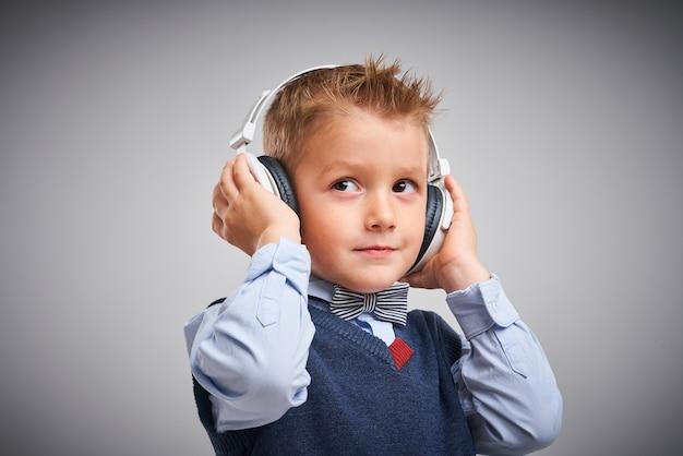 Retrato de um menino posando sobre branco com fones de ouvido