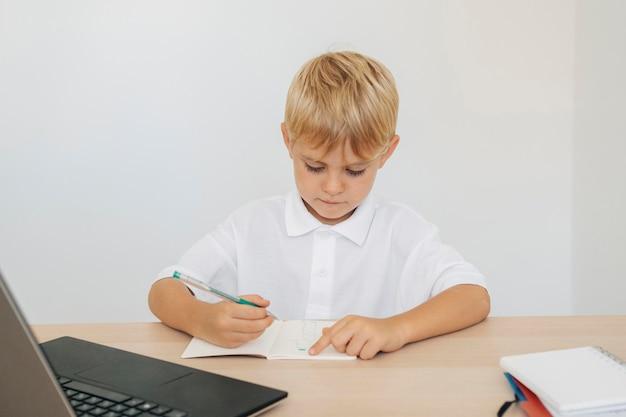 Retrato de um menino prestando atenção nas aulas online