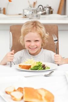 Retrato de um menino pronto para comer macarrão e salada