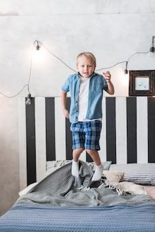 Retrato, de, um, menino, pular, cama, com, decorado, luz iluminada, ligado, parede