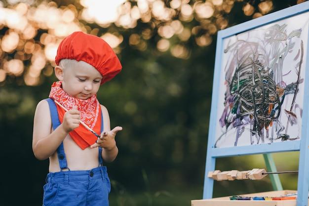Retrato de um menino que sorri com vergonha e se alegra com a pintura nas mãos dela