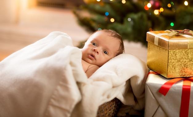 Retrato de um menino recém-nascido deitado debaixo do cobertor ao lado da árvore de natal e de caixas de presente
