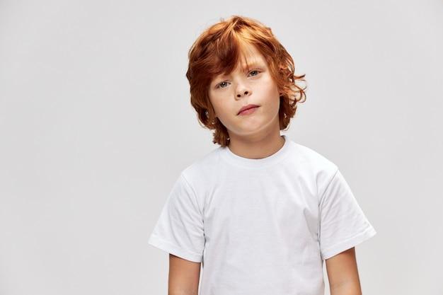 Retrato de um menino ruivo em uma camiseta branca com a cabeça de um lado