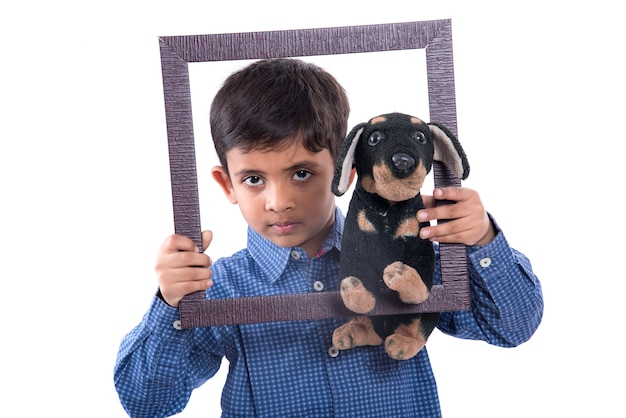 Retrato de um menino segurando um animal de estimação de pelúcia com moldura