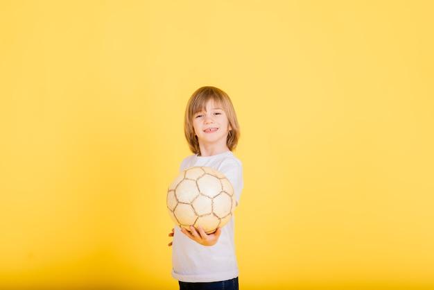 Retrato de um menino segurando uma bola de futebol, fundo amarelo estúdio