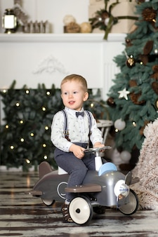 Retrato de um menino sentado em um avião de brinquedo vintage perto de uma árvore de natal. decorações de natal. o menino se alegra com seu presente de natal. feliz natal e feliz ano novo